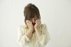 両手を目に当て泣く若い女性
