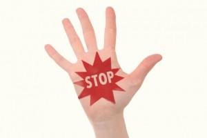 手のひらに赤字で書かれたSTOPの文字