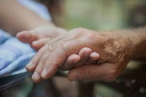 老人の手を取り重なり合う二つの手