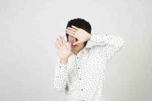 両手で顔を隠して身を守る若い男性