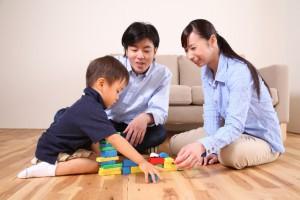 幼い子供とブロックで遊ぶ若い夫婦