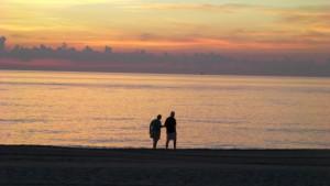 夕日の浜辺を歩く老夫婦