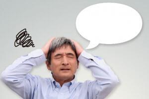 頭を抱えて悩む年配の男性