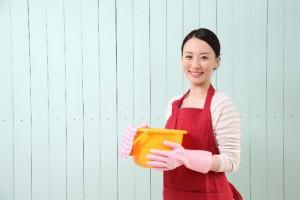 清掃用バケツを両手で持って微笑む若い女性