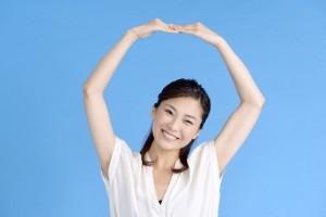 大きく両腕で丸を作る女性