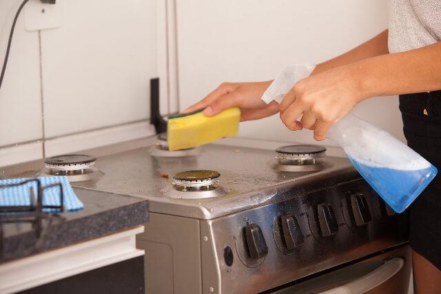キッチンガスコンロを清掃するハウスクリーニング士