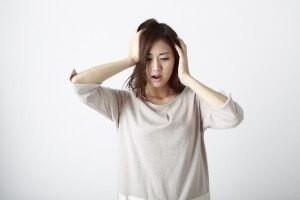 両手で頭を抱えて悩む若い女性