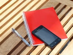 ベンチの上に置かれたノートとスマートフォン・ボールペン