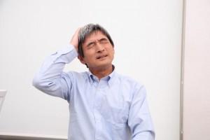 頭に手を置き悩む年配の男性
