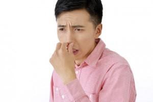 鼻をつまんで嫌そうな顔をする若い男性
