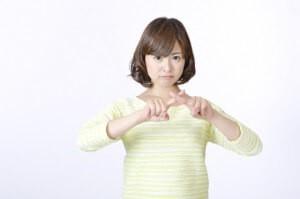 胸の前に両手でバツを作る若い女性