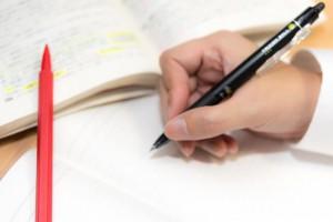 参考書とボールペンを握る手