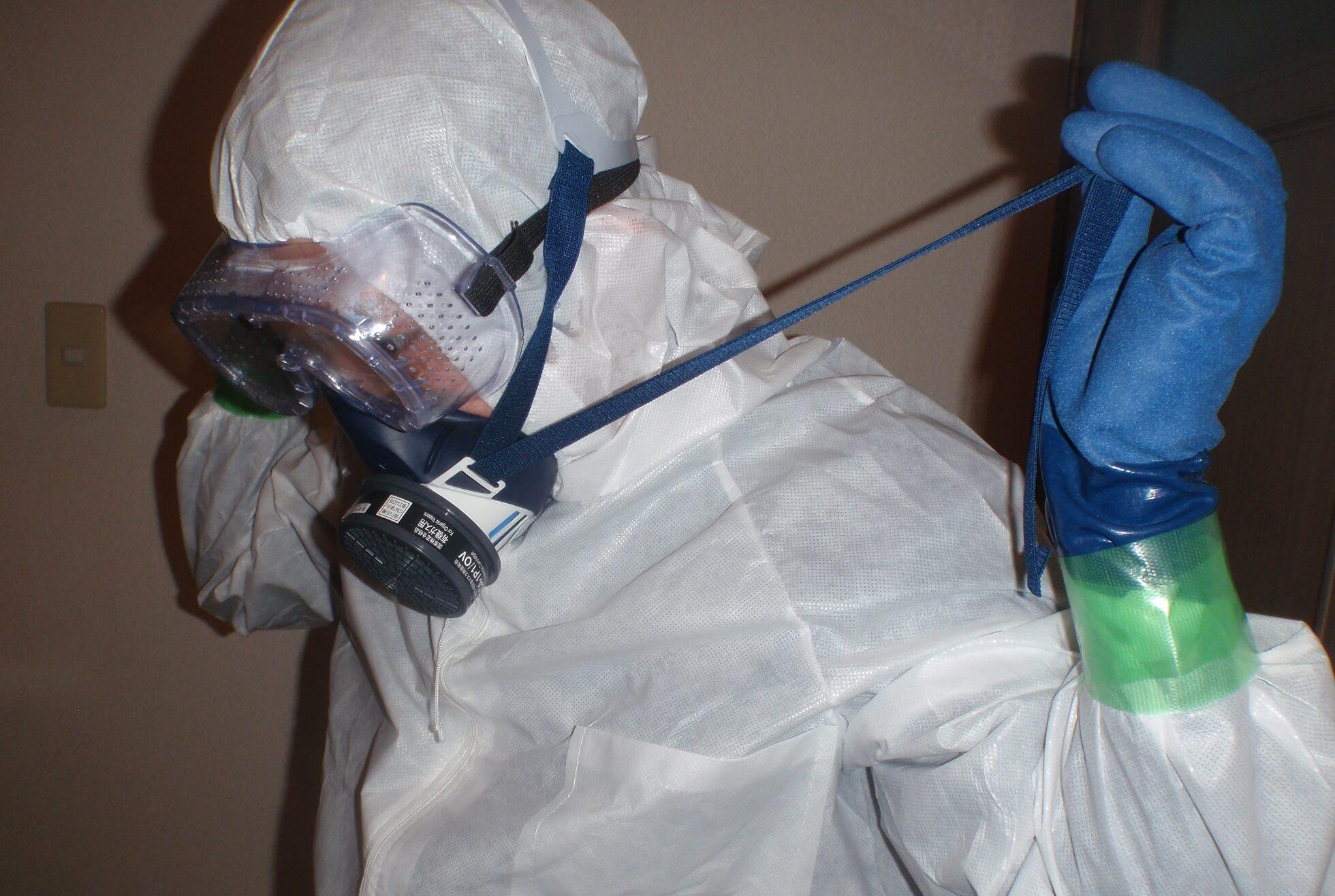 防護服と防毒マスクを着用した事件現場特殊清掃士